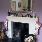 Fireplace adorned with ivy, candles & stockings
