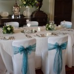 Chairs dressed in white with teal blue organza